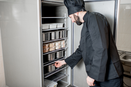 Photo for Chef cook getting a tray with ingredients from the professional refrigerator in the kitchen - Royalty Free Image