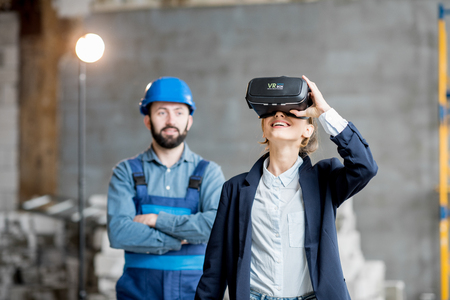Foto per Woman client wearing VR glasses imagining future interior standing with builder at the construction site - Immagine Royalty Free