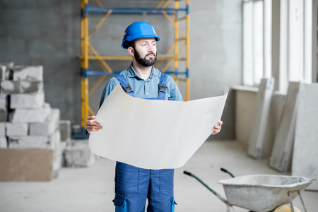 Photo pour Builder or foreman in working uniform expertising the structure standing with blueprint at the construction site indoors - image libre de droit
