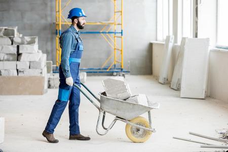 Foto de Builder carrying blocks on a wheelbarrow at the construction site indoors - Imagen libre de derechos