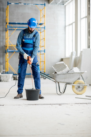 Foto de Builder in uniform mixing plaster with drill at the construction site indoors - Imagen libre de derechos