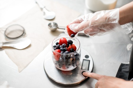 Photo for Putting berries into the small jar weighting ingredients for the ice cream production - Royalty Free Image
