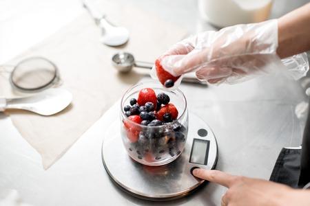 Foto de Putting berries into the small jar weighting ingredients for the ice cream production - Imagen libre de derechos