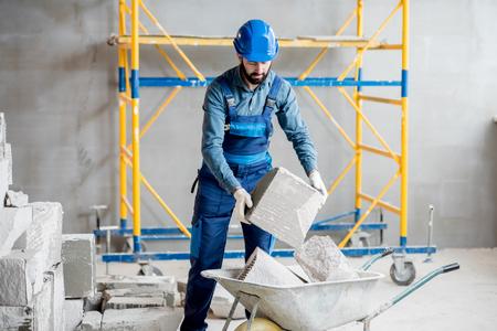 Foto de Builder in uniform working with building blocks at the construction site indoors - Imagen libre de derechos