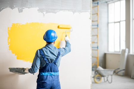 Photo for Workman in uniform painting wall with yellow paint at the construction site indoors - Royalty Free Image