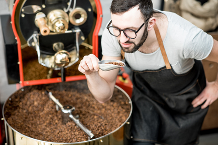 Foto de Man checking the quality of the coffee beans standing with scoop near the roaster machine at the roastery - Imagen libre de derechos