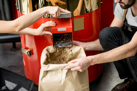Foto de Pouring roasted coffee beans into the paper bag from the roaster machine for selling - Imagen libre de derechos