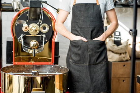 Foto de Barista in apron with hands in the pockets standing near the roaster machine - Imagen libre de derechos