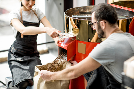 Foto de Couple pouring roasted coffee beans into the paper bag from the roaster machine for selling - Imagen libre de derechos