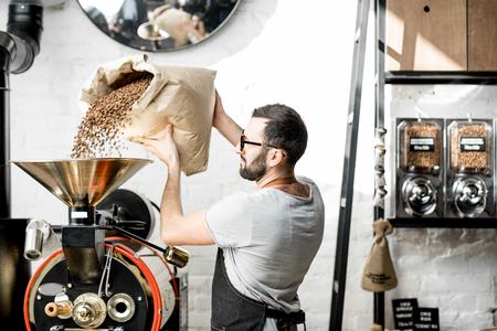 Foto de Man pouring coffee beans into the roaster machine indoors - Imagen libre de derechos