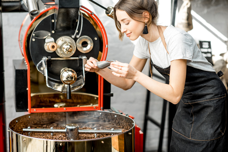 Foto de Woman checking the quality of the coffee beans standing with scoop near the roaster machine at the roastery - Imagen libre de derechos