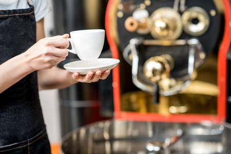 Foto de Waiter in uniform holding a coffee cup with roaster machine on the background. Close-up view on the cup - Imagen libre de derechos