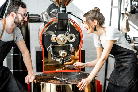 Foto de Couple of two baristas checking the quality of the coffee beans standing with scoop near the roaster machine at the roastery - Imagen libre de derechos