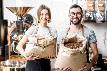 Foto de Portrait of a two happy baristas in uniform standing with bags full of coffee beans at the coffee store - Imagen libre de derechos