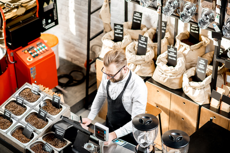 Foto de Sales man standing at the counter in the coffee store with roaster machine on the background - Imagen libre de derechos