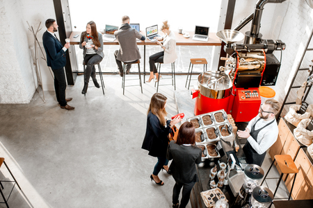 Foto de Business people talking and having fun durnig a coffee time in the modern cafe interior. Wide view from above - Imagen libre de derechos