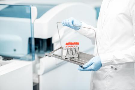 Foto de Laboratory assistant holding test tubes near the analyzer machine - Imagen libre de derechos