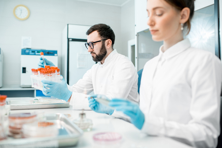 Foto de Couple of medics in uniform making bacteriological tests sitting in the modern laboratory - Imagen libre de derechos