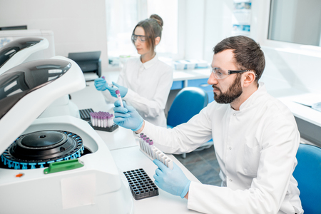 Foto de Laboratory assistants making analysis with test tubes and analyzer machines sitting at the modern laboratory - Imagen libre de derechos