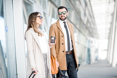 Photo for Business couple in coats walking out the airport with luggage during the business trip - Royalty Free Image