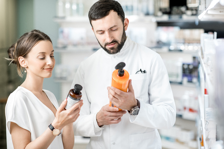 Foto de Pharmacist helping young woman client to choose cosmetics at the pharmacy store - Imagen libre de derechos