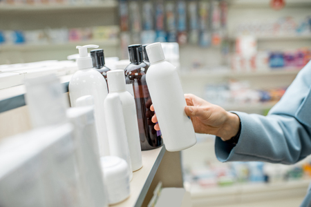 Photo pour Woman taking a bottle with cosmetics from the shelf of the pharmacy supermarket, close-up view on the bottle with blank label - image libre de droit
