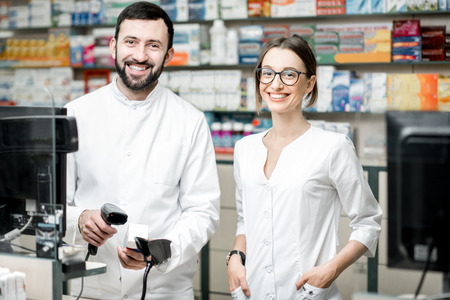 Foto de Portrait of a two pharmacists working at the paydesk selling medications in the pharmacy store - Imagen libre de derechos