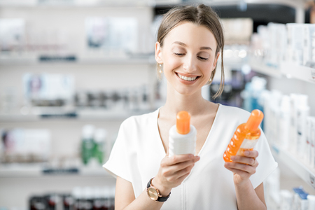 Photo pour Young woman customer choosing sunscreen lotion at the pharmacy store - image libre de droit