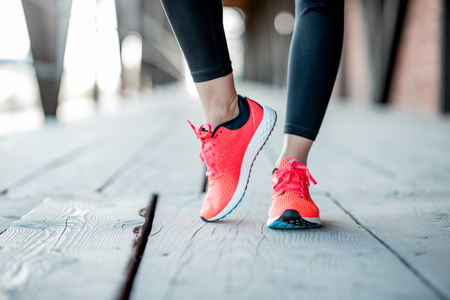 Photo pour Sports woman in running shoes standing on the wooden floor, close-up view focused on the sneakers - image libre de droit