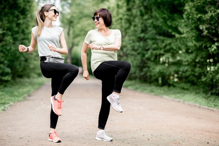 Photo pour Young and elder sports woman stretching in the park during the morning exesrcise - image libre de droit