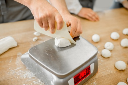 Photo pour Baker weighing dough portions for baking buns at the manufacturig, close-up view - image libre de droit