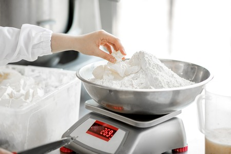 Foto de Weighing flour for baking with professional scales at the manufacturing, close-up view - Imagen libre de derechos