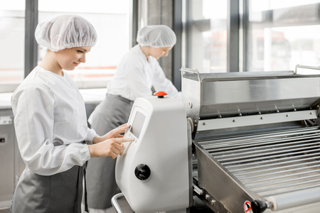 Photo pour Women in uniform working with dough rolling machine at the bakery manufacturing - image libre de droit