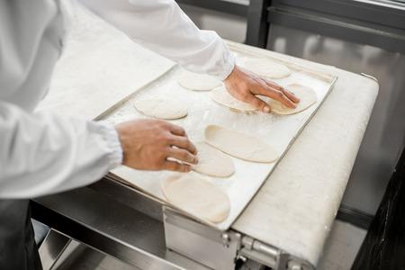 Foto de Putting raw dough workpieces for buns making at the bakery manufacturing - Imagen libre de derechos