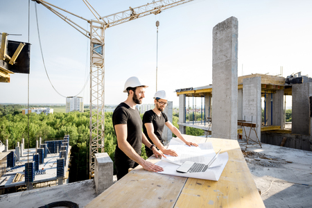 Photo pour Two workers in black t-shirts and protective harhats working with drawings at the construction site outdoors - image libre de droit