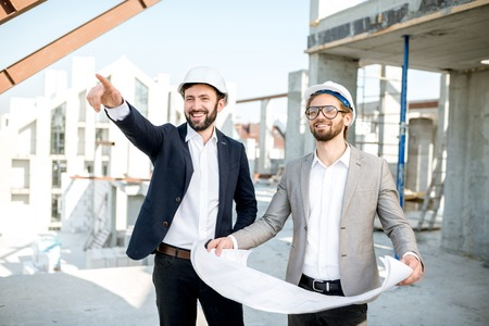 Foto de Two business men or engeneers working with house drawings on the structure during the construction process outdoors - Imagen libre de derechos