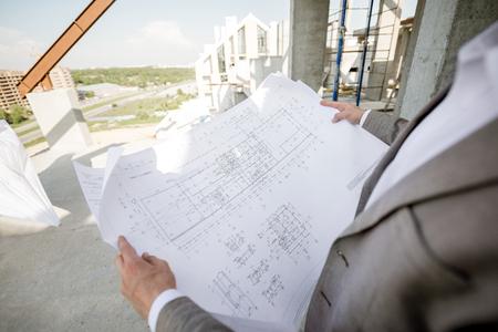 Foto de Man holding house plan drawings on the structure outdoors - Imagen libre de derechos