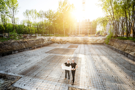 Foto de Wide angle view on the concrete foundation at the construction site with two builders standing with drawings during the sunset - Imagen libre de derechos