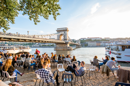 Foto de HUNGARY, BUDAPEST - MAY 18, 2018: View on the famous Chain bridge on Danube river with people relax on the riverside during the sunset - Imagen libre de derechos