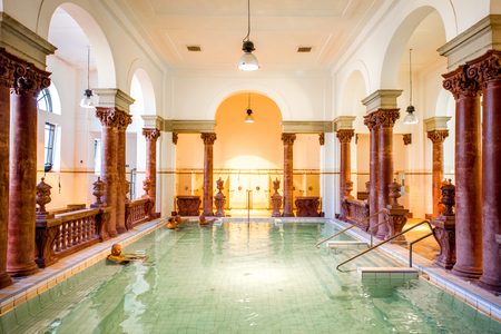 Photo for HUNGARY, BUDAPEST - MAY 21, 2018: Interior of the famous Szechenyi medicinal bath with people relaxing indoors. This place is the largest bath in Europe with thermal springs - Royalty Free Image