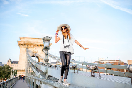 Foto de Young woman tourist walking on the old Chain bridge during the sunset traveling in the Budapest - Imagen libre de derechos