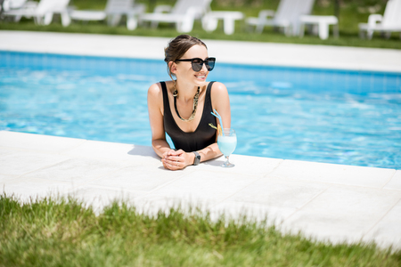 Photo pour Portrait of a beautiful woman in black swimsuit relaxing with cocktail at the swimming pool outdoors - image libre de droit