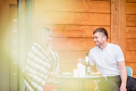 Photo pour Lovely couple during a romantic dinner on the terrace of their wooden country house - image libre de droit