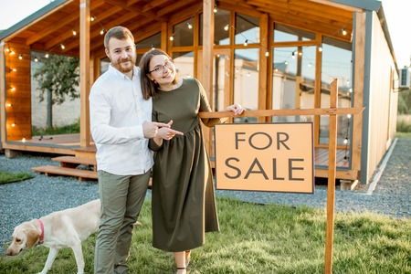 Photo for Elegant couple standing with dog near the beautiful wooden country house for sale - Royalty Free Image