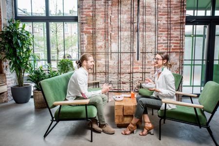 Foto de Business people sitting on the green sofas during a lunch at the beautiful loft interior on the brick wall background - Imagen libre de derechos