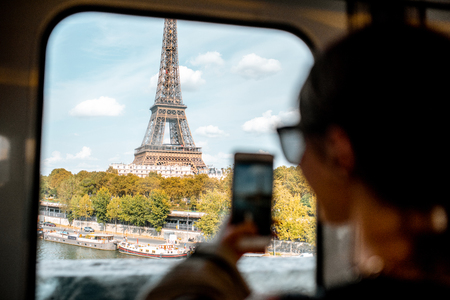 Foto de Young woman photographing with smartphone Eiffel tower from the subway train in Paris. Image focused on the tower - Imagen libre de derechos