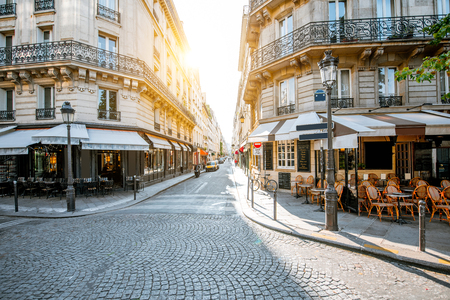 Photo pour Street view with beautiful buildings and cafe terrace during the morning light in Paris - image libre de droit