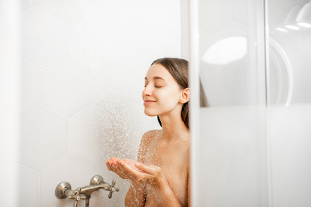 Photo for Young and beautiful woman washing her face, taking a shower in the white cabin - Royalty Free Image
