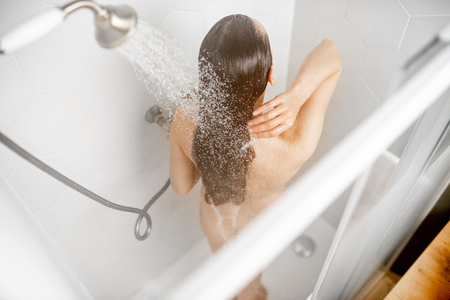 Foto de Woman washing her beautiful long hair, while taking a shower standing back in the shower cabin. View from above - Imagen libre de derechos