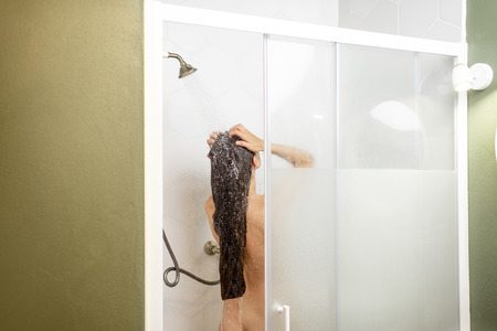 Photo pour Woman washing her beautiful long hair, while taking a shower standing back in the shower cabin. Wide view with copy space on the wall - image libre de droit